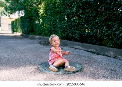 Little girl sits and cries on the manhole in the park