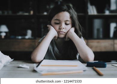 Little Girl Sits at Desk Shows Bored Expression. Portrait of Black-Haired Child Keeps Head in Hands and Looks at White Notebook with Pencil Lying on Table. Boredom and Idleness Concept
