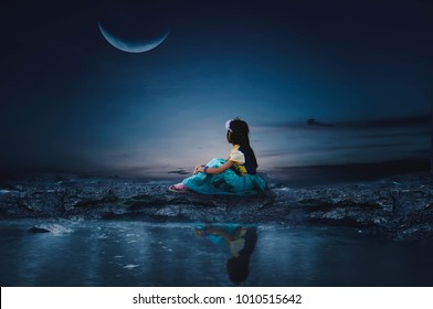 The little girl sits in the moonlight on a beautiful night.
