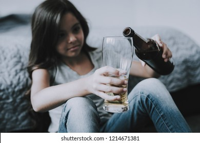 Little Girl Sits near Bed and Pours Beer in Glass. Unhappy Black-Haired Caucasian Difficult Child Wearing Gray T-Shirt Holds Alcohol Drink in Hand Leans on Bed Edge. Children's Alcoholism Concept
