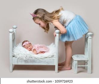 Little girl sits next her newborn sister