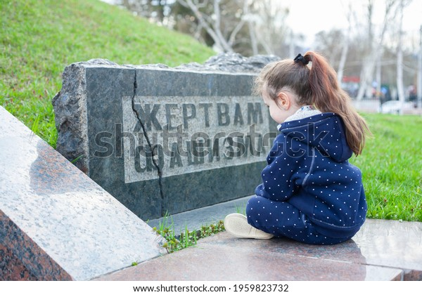 """A little girl sits next to a monument with an inscription in Russian """"Victims of Fascism"""""""