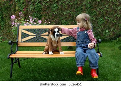 The little girl sits on a bench with the puppy of the boxer
