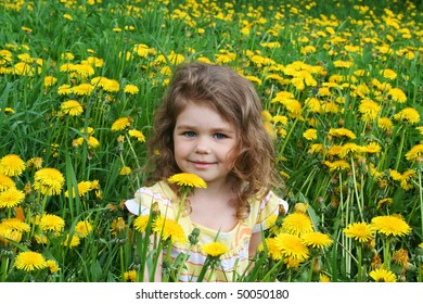 Little girl sits on a glade with dandelions