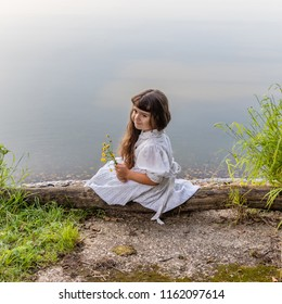 The little girl sits on the shore of a forest lake