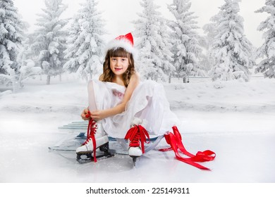 Little girl sits on a sledge and puts on the skates