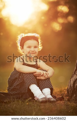 little girl sits on sunset