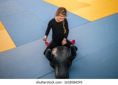 . A little girl sits on top on a training mannequin and works off punches. Children's sports activity in the gymThe child beats the training dummy with his hands