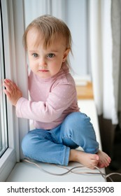 A little girl sits on the windowsill and looks out the window. The girl is a year and a half, she has short hair, jeans and a turtleneck. Dangerous situation. Child safety