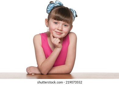 A little girl sits at a school desk against the white background