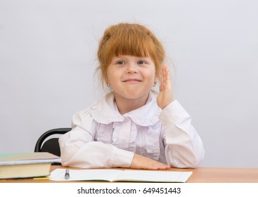 The little girl sits at a school desk, raising his hand to answer