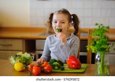 Kleines Mädchen sitzt an einem Tisch in der Küche. Sie schnitt Gemüse zum Salat. Auf dem Küchentisch stehen zahlreiche Veggies und Grünpflanzen. Das Mädchen mag den Geschmack natürlicher Produkte. Gesunde Lebensmittel seit der Kindheit.