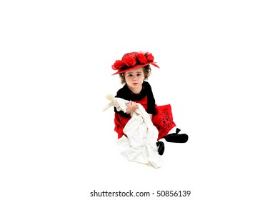 Little girl sits in white room holding an old fashioned rag doll and wearing an old fashioned straw hat. Her dress is black velvet and red tulle with embroidery in black.