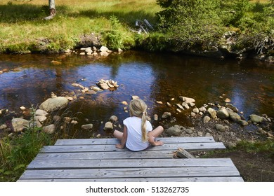 Little girl sitting alone on a pier near the small river.