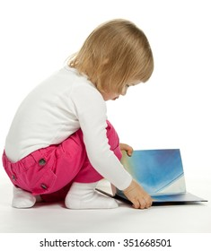 The little girl sitting among books and turning over the pages; white background