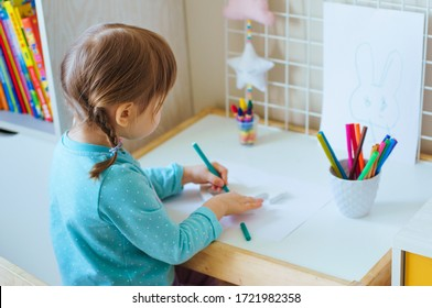 Little girl sitting back drawing with felt-tip pen sitting at the table in the kids room.  Selective focus.