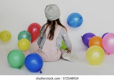 Little girl sitting balloons studio