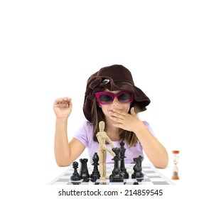 Little Girl sitting behind Mannequin on chess board next to hour glass isolated on white background