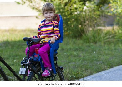 Little girl sitting in bicycle seat