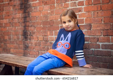 Little Girl sitting by brick wall