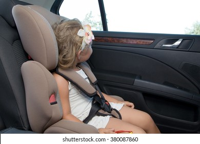 Little girl sitting in  car seat looking out the car window