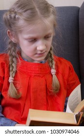 little girl is sitting in a chair and is reading a book
