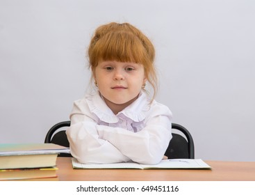 Little girl sitting at the desk with his hands folded in front of him
