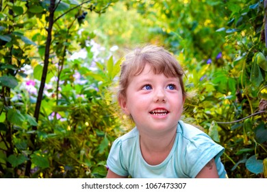 little girl is sitting in flower bush. Baby is smiling on a background of green grass. Lucky moment of childhood.