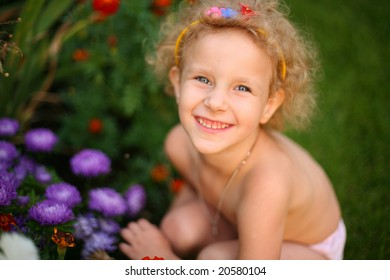 A little girl sitting in the flowers