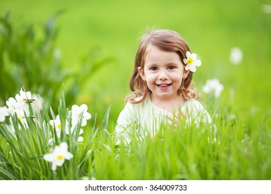 Little girl sitting in grass and smiling