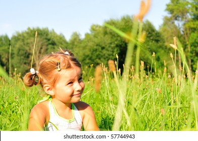 Little girl sitting in the green grass