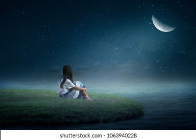 A little girl sitting half moon in the grass in the middle of the water in a lonely night.