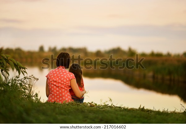 Little girl sitting with her mother near the lake,back view