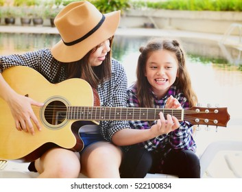 A little girl sitting with her older sister that playing guitar at outside home. Soft focus on a warm light evening.