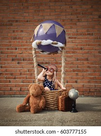 A little girl is sitting in a hot air balloon basket in the park pretending to travel and fly with a pilot hat on for a creativity or imagination concept.