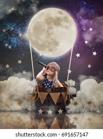 A little girl is sitting in a hot air balloon moon basket with stars in the sky pretending to travel and fly with a pilot hat on for a creativity or imagination concept.