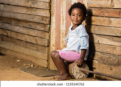Little girl sitting infront of  shack with a happy expression on her face