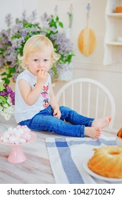 Little girl is sitting in the kitchen on the table and eating a cookie
