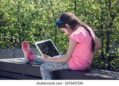 Little girl sitting with laptop in the park.