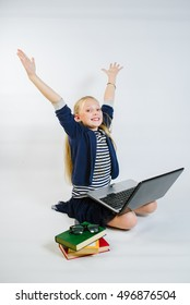 Little girl sitting at the laptop and rised her hands up on the white background