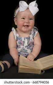 A little girl sitting and laughing at something funny in the book she is reading.