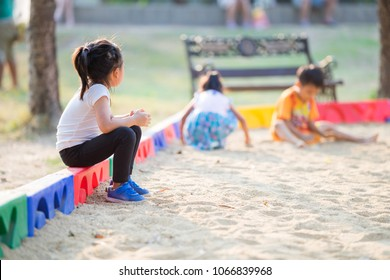 Little girl sitting lonely watching friends play at the playground.The feeling was overlooked by other people.