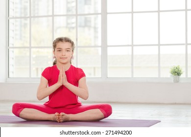 Little girl sitting in Namaste position at fitness studio with big windows on background