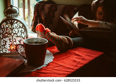 Little girl sitting near the window with a cup of hot drink and reading a book.