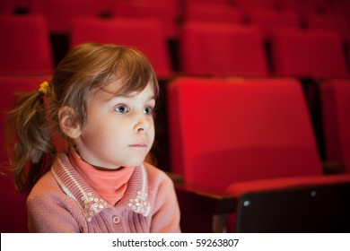 little girl sitting on armchairs at cinema, steadfastly looking