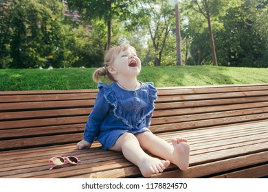 Little girl sitting on the bench and laughing in a city park on a warm sunny day