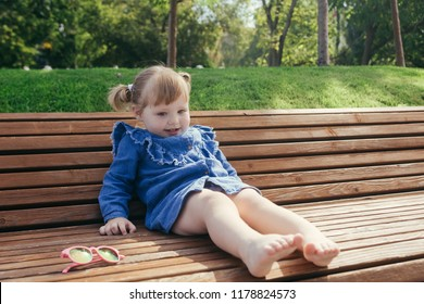 Little girl sitting on the bench in a city park on a warm sunny day