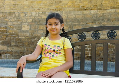 Little girl sitting on the bench