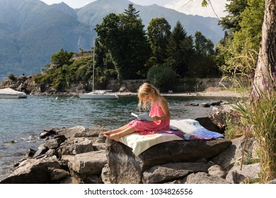 little girl sitting on a big rock and reading a book at the stony beach of the Lago Maggiore in Italy