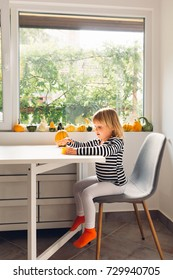 Little girl sitting on a chair in the dining room